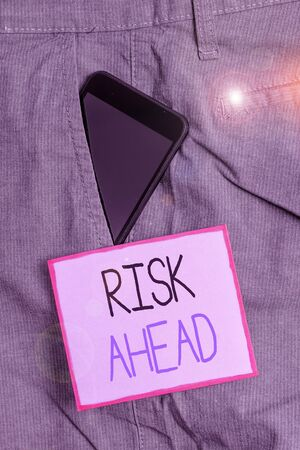 Text sign showing Risk Ahead. Business photo showcasing A probability or threat of damage, injury, liability, loss Smartphone device inside formal work trousers front pocket near note paper
