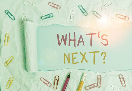 Conceptual hand writing showing What S Next Question. Concept meaning asking demonstrating about his coming actions or behaviors Stationary and torn cardboard on a plain pastel table backdrop