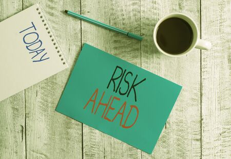 Writing note showing Risk Ahead. Business concept for A probability or threat of damage, injury, liability, loss Stationary placed next to a cup of black coffee above the wooden table