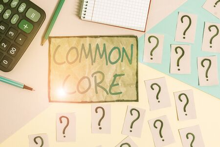 Writing note showing Common Core. Business concept for set of academic standards in mathematics and English language Mathematics stuff and writing equipment above pastel colours background