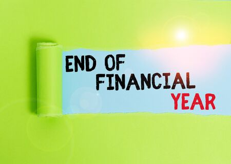 Text sign showing End Of Financial Year. Business photo text Revise and edit accounting sheets from previous year Cardboard which is torn in the middle placed above a plain table backdrop Stock Photo