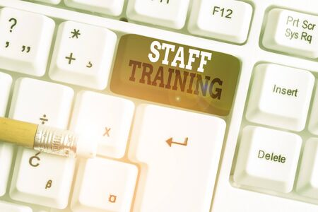 Text sign showing Staff Training. Business photo text program that helps employees learn specific knowledge White pc keyboard with empty note paper above white background key copy space