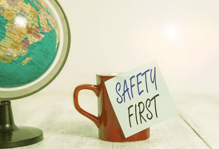 Conceptual hand writing showing Safety First. Concept meaning used to say that the most important thing is to be safe Globe map coffee cup sticky note lying vintage wooden table