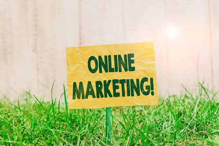 Word writing text Online Marketing. Business photo showcasing leveraging web based channels spread about companys brand Plain empty paper attached to a stick and placed in the green grassy land