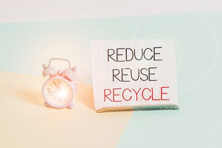 Conceptual hand writing showing Reduce Reuse Recycle. Concept meaning ways can eliminate waste protect your environment Alarm clock beside a Paper sheet placed on pastel backdrop