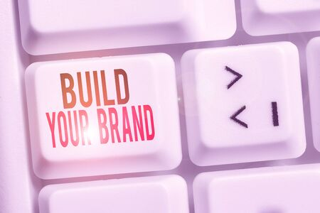 Handwriting text Build Your Brand. Conceptual photo enhancing brand equity using advertising campaigns White pc keyboard with empty note paper above white background key copy space