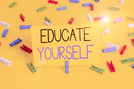 Text sign showing Educate Yourself. Business photo text prepare oneself or someone in a particular area or subject Colored clothespin papers empty reminder yellow floor background office Reklamní fotografie