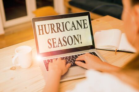 Word writing text Hurricane Season. Business photo showcasing time when most tropical cyclones are expected to develop woman laptop computer smartphone mug office supplies technological devices