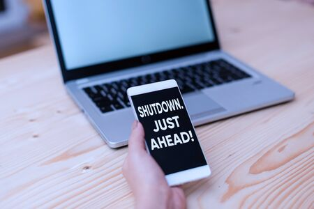 Conceptual hand writing showing Shutdown Just Ahead. Concept meaning closing factory business either short time or forever woman with laptop smartphone and office supplies technology