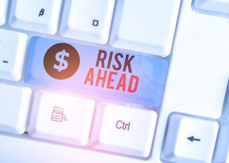 Writing note showing Risk Ahead. Business concept for A probability or threat of damage, injury, liability, loss White pc keyboard with note paper above the white background