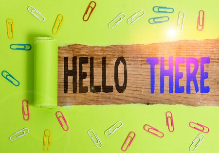 Text sign showing Hello There. Business photo text a way to get someone s is attention more strongly upon greeting Paper clip and torn cardboard placed above a wooden classic table backdrop