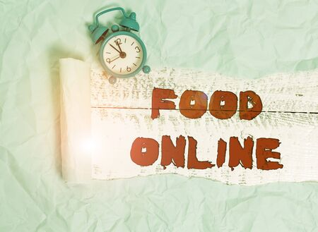 Conceptual hand writing showing Food Online. Concept meaning most convenient way for customers to purchase food online Alarm clock and torn cardboard on a wooden classic table backdrop