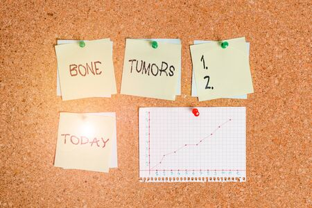 Conceptual hand writing showing Bone Tumors. Concept meaning can be either benign or malignant growths found in the bone Corkboard size paper thumbtack sheet billboard notice board Banco de Imagens