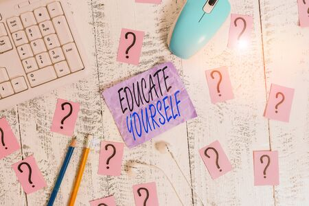 Writing note showing Educate Yourself. Business concept for prepare oneself or someone in a particular area or subject Writing tools and scribbled paper on top of the wooden table