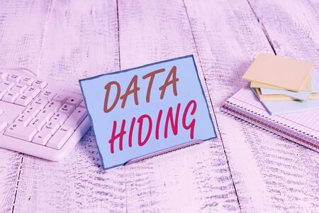 Word writing text Data Hiding. Business photo showcasing Secretly embedding data in graphics images and other file types Notepaper stand on buffer wire in between computer keyboard and math sheets Stock Photo - 133738065