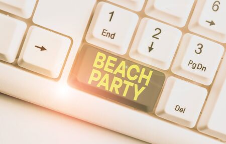 Writing note showing Beach Party. Business concept for large group of showing are organizing an event at the beach White pc keyboard with note paper above the white background Stock fotó