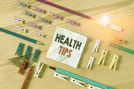 Word writing text Health Tips. Business photo showcasing advice or information given to be helpful in being healthy Colored clothespin papers empty reminder wooden floor background office Stock Photo