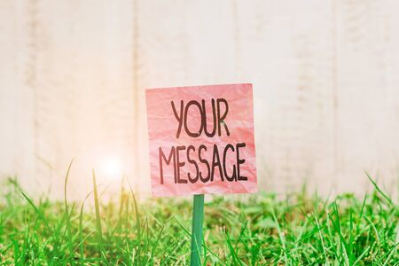 Conceptual hand writing showing Your Message. Concept meaning piece of information or a request that you send to someone Plain paper attached to stick and placed in the grassy land