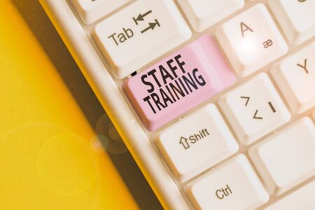 Text sign showing Staff Training. Business photo showcasing program that helps employees learn specific knowledge White pc keyboard with empty note paper above white background key copy space