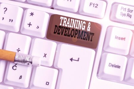 Text sign showing Training And Development. Business photo text learn specific knowledge to improve perforanalysisce White pc keyboard with empty note paper above white background key copy space