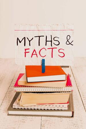Conceptual hand writing showing Myths And Facts. Concept meaning usually traditional story of ostensibly historical events pile stacked books notebook pin color reminder white wooden