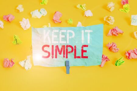 Conceptual hand writing showing Keep It Simple. Concept meaning to make something easy to understand and not in fancy way Colored crumpled paper empty reminder white floor clothespin Stock Photo
