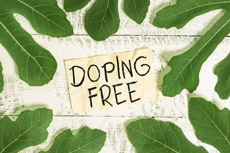 Conceptual hand writing showing Doping Free. Concept meaning proven not using any substance to illegally improve athletic Leaves surrounding notepaper above a classic wooden table