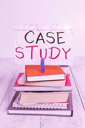 Conceptual hand writing showing Case Study. Concept meaning analysis and a specific research design for examining a problem pile stacked books notebook pin color reminder white wooden Reklamní fotografie