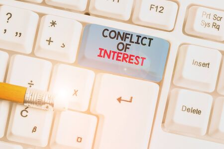 Writing note showing Conflict Of Interest. Business concept for disagreeing with someone about goals or targets White pc keyboard with note paper above the white background