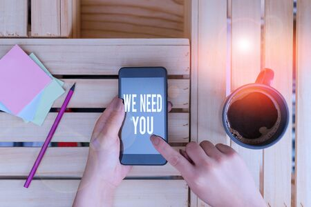 Conceptual hand writing showing We Need You. Concept meaning to fulfill the needs of the assignment duty or obligation woman with laptop smartphone and office supplies technology