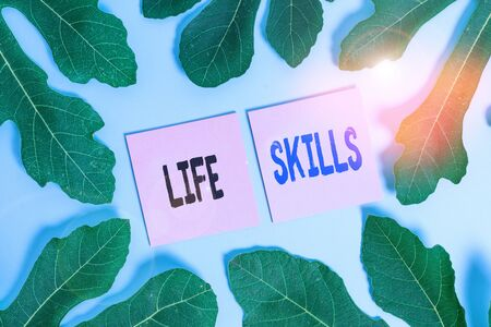 Text sign showing Life Skills. Business photo text skill that is necessary for full participation in everyday life Leaves surrounding notepaper above an empty soft pastel table as background