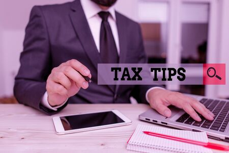 Conceptual hand writing showing Tax Tips. Concept meaning compulsory contribution to state revenue levied by government Male human wear formal clothes present use hitech smartphone Stok Fotoğraf