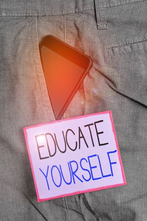 Text sign showing Educate Yourself. Business photo showcasing prepare oneself or someone in a particular area or subject Smartphone device inside formal work trousers front pocket near note paper