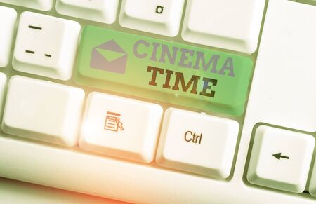 Handwriting text Cinema Time. Conceptual photo which entertainment such showing movie scheduled to start White pc keyboard with empty note paper above white background key copy space Stock fotó