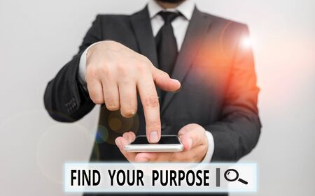 Text sign showing Find Your Purpose question. Business photo text reason for something is done or for which exists Male human wear formal work suit hold smart hi tech smartphone use one hand Standard-Bild - 133473101