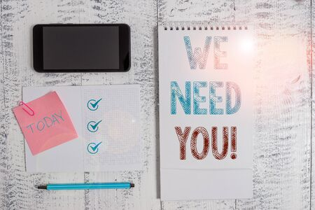 Writing note showing We Need You. Business concept for to fulfill the needs of the assignment duty or obligation Square spiral notebook marker smartphone sticky note on wood background