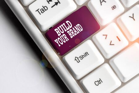 Text sign showing Build Your Brand. Business photo showcasing enhancing brand equity using advertising campaigns White pc keyboard with empty note paper above white background key copy space Фото со стока