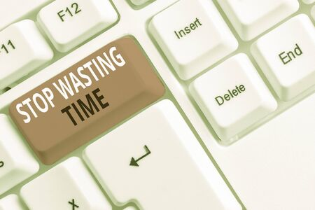 Text sign showing Stop Wasting Time. Business photo showcasing advising demonstrating or group start planning and use it wisely White pc keyboard with empty note paper above white background key copy space