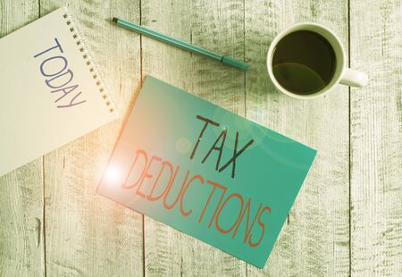 Writing note showing Tax Deductions. Business concept for an amount or cost that subtracted from someone s is income Stationary placed next to a cup of black coffee above the wooden table