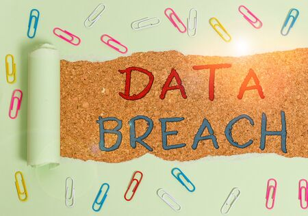 Handwriting text Data Breach. Conceptual photo incident in which sensitive or confidential data is copied Paper clip and torn cardboard placed above a wooden classic table backdrop
