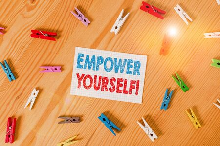 Handwriting text writing Empower Yourself. Conceptual photo taking control of our life setting goals and making choices Colored clothespin papers empty reminder wooden floor background office