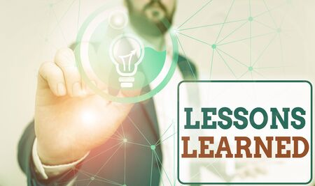 Writing note showing Lessons Learned. Business concept for the knowledge or understanding gained by experience Male human wear formal suit presenting using smart device