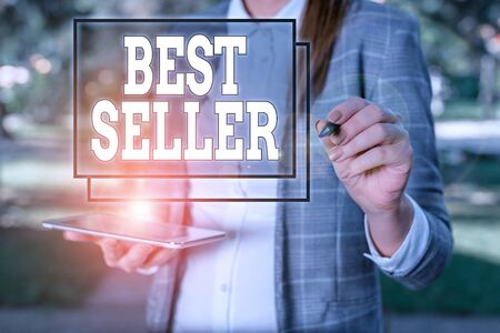 Handwriting text Best Seller. Conceptual photo new book or other product that has sold a great number of copies Outdoor background with business woman holding lap top and pen Stok Fotoğraf