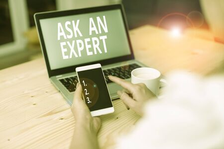 Text sign showing Ask An Expert. Business photo text consult someone who has skill about something or knowledgeable woman laptop computer smartphone mug office supplies technological devices Standard-Bild - 133474689