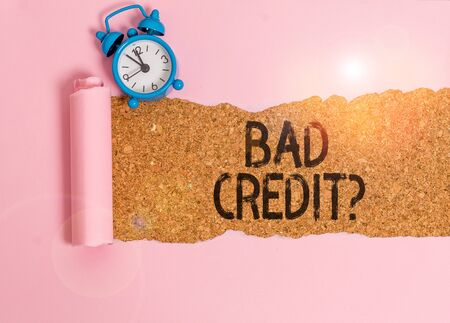 Text sign showing Bad Creditquestion. Business photo showcasing inabilityof a demonstrating to repay a debt on time and in full Alarm clock and torn cardboard placed above a wooden classic table backdrop Stok Fotoğraf