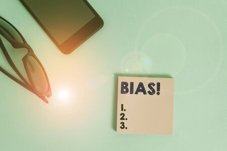 Text sign showing Bias. Business photo showcasing inclination or prejudice for or against one demonstrating group Dark eyeglasses colored sticky note smartphone fashion pastel background 版權商用圖片