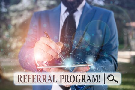 Writing note showing Referral Program. Business concept for employees are rewarded for introducing suitable recruits Male human wear formal suit presenting using smart device
