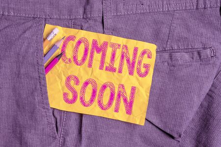 Word writing text Coming Soon. Business photo showcasing something is going to happen soon or after a short time Writing equipment and yellow note paper inside pocket of man work trousers Stock Photo