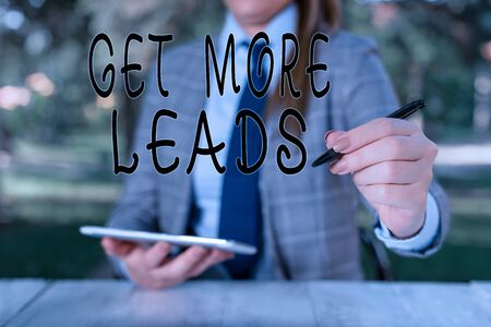 Writing note showing Get More Leads. Business concept for to have more customers and improve your target sales Female business person sitting by table holding mobile phone