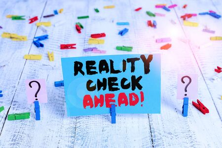 Text sign showing Reality Check Ahead. Business photo showcasing makes them recognize truth about situations or difficulties Scribbled and crumbling sheet with paper clips placed on the wooden table
